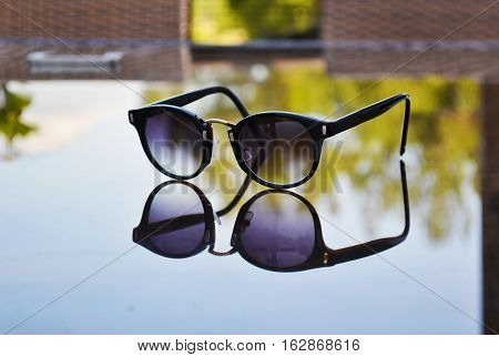 sunglasses reflection on table - fashion accessories