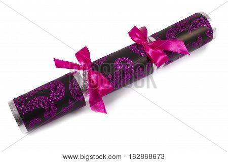 A studio shot of a Cracker or otherwise known as a Bon Bon. A traditional cracker consists of a cardboard tube wrapped in a brightly decorated twist of paper with a gift in the central chamber.