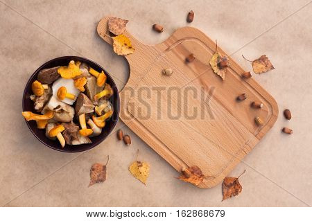 Raw Food. Bowl With Raw Cut Edible Mushrooms (Chanterelle Cep) And Cutting Wooden Board On Beige Brown Background Top View.