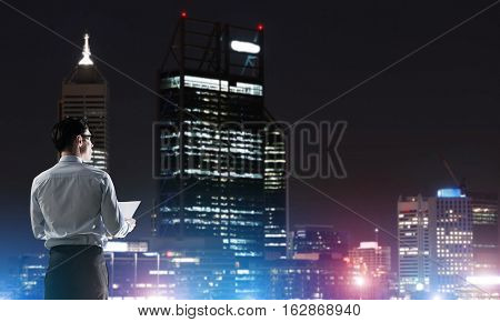 Elegant businessman with suitcase looking at night city