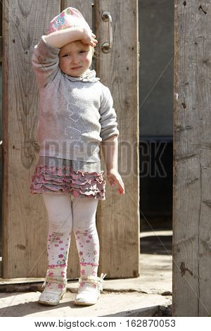 STINKA UKRAINE - APRIL 14 2016 - funny little girl stands in a wicket and covers by hand on April 14 2016 in Stinka village.