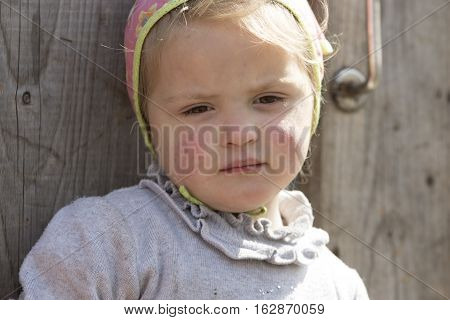 STINKA UKRAINE - APRIL 14 2016 - sad little girl closeup looks down standing at the wicket on April 14 2016 in Stinka village.