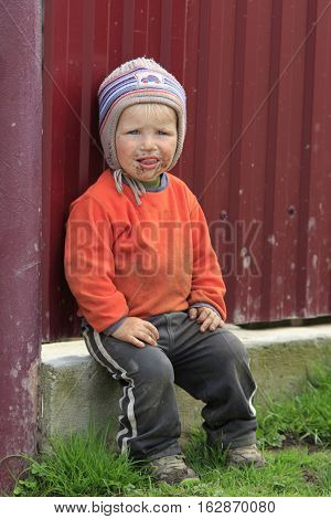 STINKA UKRAINE - APRIL 14 2016 - funny little dirty boy with his tongue out sits at the fence on April 14 2016 in Stinka village