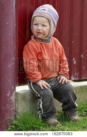 STINKA UKRAINE - APRIL 14 2016 - little funny slut boy dressed in dirty clothes sits in a yard on April 14 2016 in Stinka village.