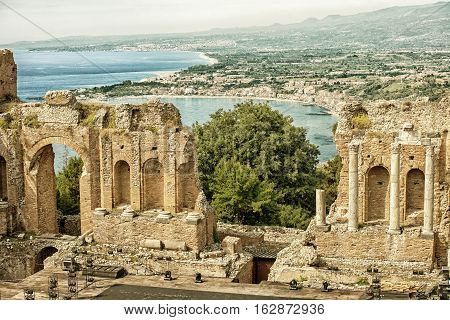 The ancient -roman-greek amphitheatre with the Giardini Naxos bay in the back in Taormina city Sicily Italy (HDR image with black and gold filters)