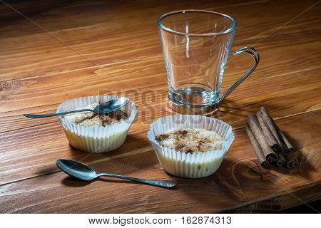 Two cups of rice pudding with cinnamon sticks on a wooden table