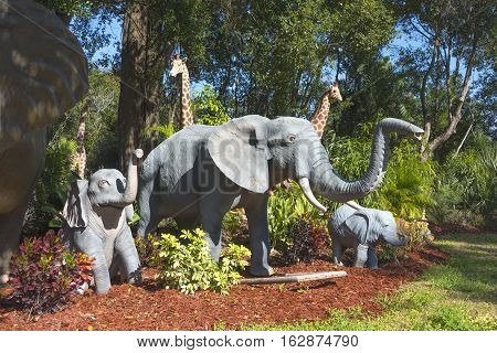 Gotha Florida - December 22nd 2016: Garden statues of an Adult elephant and two baby elephants with Giraffes in the background in Gotha Florida - December 22nd 2016