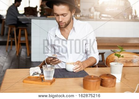 Handsome Man Wearing White Shirt And Black Stylish Hat Using Wireless Internet Connection On His Mob