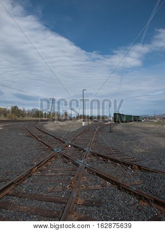 Railroad tracks crossing at a junction North of Redmond in Central Oregon with freight cars in the background on a spring day.