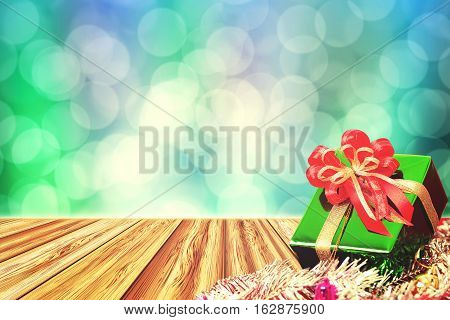 Gift box on perspective wood table with abstract twinkling lights blurred bokeh background for christmas and new year celebration. Cross process and vintage tone.