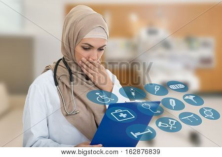 portrait of worried muslim female Medical doctor holding paperclip. Medical simbols