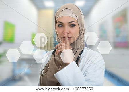 Closeup portrait of friendly, confident muslim with hijab doctor showing shh sigh, silence, healthcare professional in modern hospital