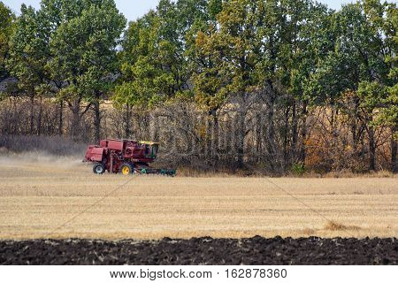Harvester is working in the field during harvest time.