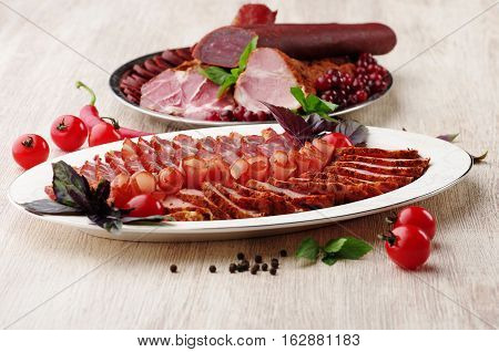 Deli meat on plate. light wood, restaurant serving.