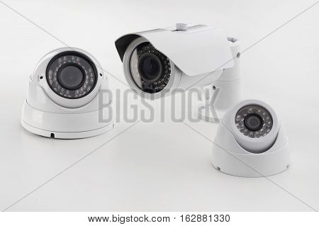 Bullet style and dome secure camera on light background, surveillance cameras.
