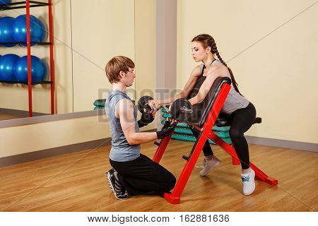 Coach man helping woman exercise for biceps with barbell. Personal trainer. Healthy lifestyle concept. Fitness.