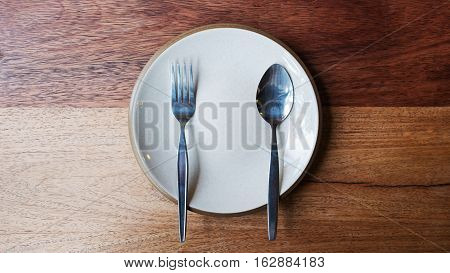 Empty plate with spoon and fork on wooden background. Plate with spoon and fork for food