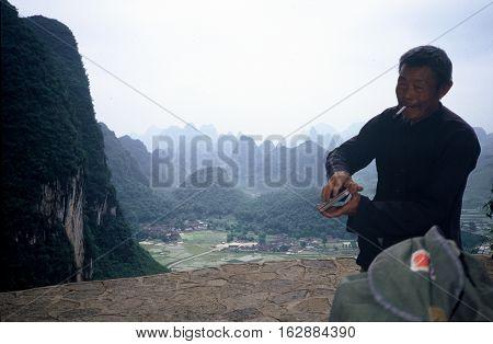 YANGSHUO / CHINA - CIRCA 1987: A souvenir seller smokes a cigarette on a mountain overlook near Yangshuo.