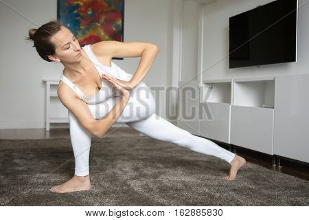 Sporty beautiful young woman practicing yoga, standing in Revolved Side Angle exercise, Parivrtta Parsvakonasana pose, working out, wearing sportswear, indoor full length, home interior background
