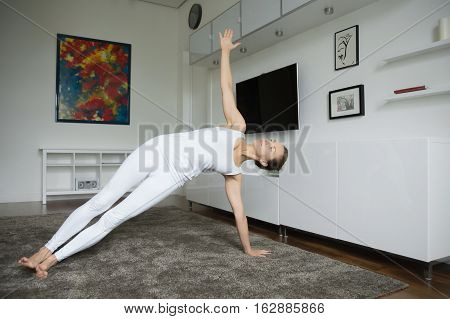 Sporty beautiful young woman practicing yoga, standing in Side Plank exercise, Vasisthasana pose, working out, wearing white sportswear, indoor full length, home interior background