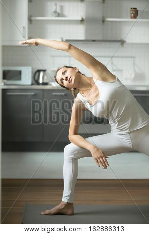 Happy sporty attractive young woman practicing yoga, standing in Extended Side Angle exercise, Utthita parsvakonasana pose, working out, wearing white sportswear, indoor, home interior background