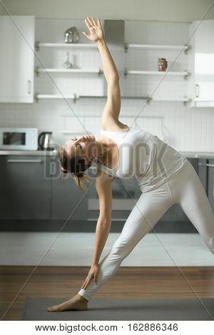 Portrait of sporty young woman practicing yoga, standing in extended triangle exercise, Utthita Trikonasana pose, working out, wearing white sportswear, indoor, home interior background
