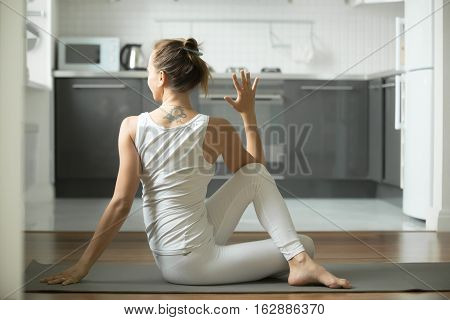 Sporty young woman practicing yoga, sitting in Half lord of the fishes exercise, Ardha Matsyendrasana pose, working out, wearing white sportswear, indoor full length, home interior background