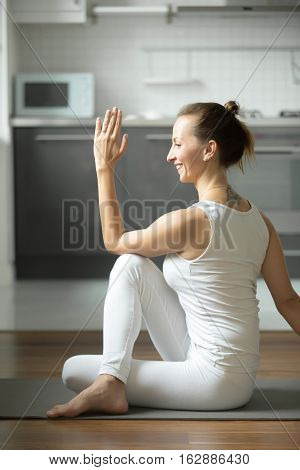 Portrait of sporty attractive woman practicing yoga, sitting in Half lord of the fishes exercise, Ardha Matsyendrasana pose, working out, wearing white sportswear, indoor, home interior background