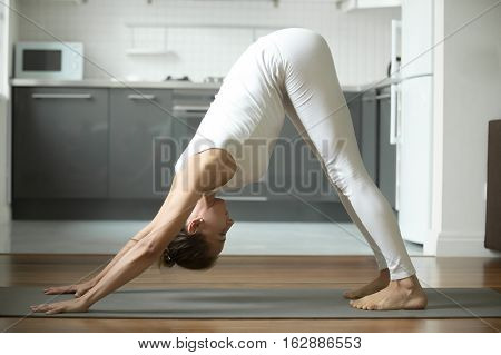 Sporty attractive woman practicing yoga, standing in Downward facing dog exercise, adho mukha svanasana pose, working out, wearing white sportswear, indoor full length, home interior background