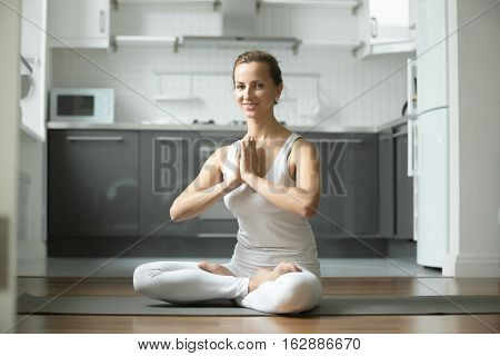Sporty attractive woman practicing yoga, sitting in Lotus exercise, Padmasana pose, working out, wearing white sportswear, indoor full length, home interior background, smiling looking at the camera