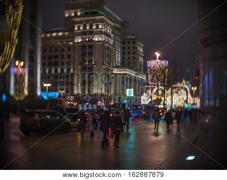 People walk along the Christmas decorated Tverskaya street view of the hotel Moscow in night