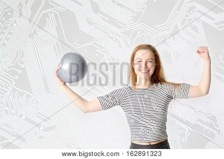 young woman athlete with strong biceps holding the ball in his hand on a computer circuit board background. Concept of education - a strong sports informatics.