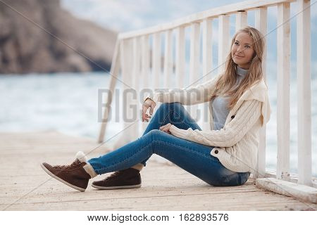 Young woman with long straight blond hair and gray eyes, dressed in a white knitted jacket, a gray turtleneck and blue jeans, spending time alone, sitting on a white wooden wharf near the blue sea on a background of mountains