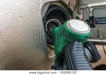 car at gas station being filled with fuel close up image