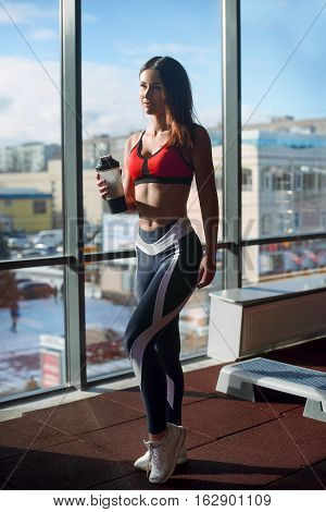 Portrait Of A Woman With A Towel Around Her Neck Holding A Protein Shaker And Standing At Gym After