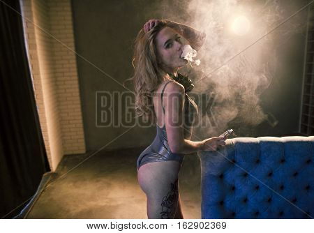 Sexy Woman Smoking Electronic Cigarette, Vaping And Clouding Indoor