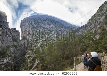 Visitors taking pictures at the begining of Caminito del Rey path Malaga Spain. Landscape with hills canyon full of morning mist