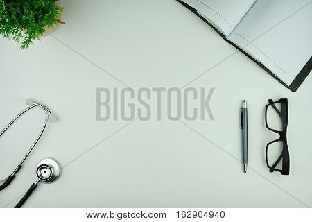 Business and Medical Concept. Top view or flat lay view of stethoscope, plant, diary, eye glasses, pen on white background.