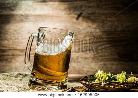 Beer in big tankard closeup standing on wooden table near hops in basket