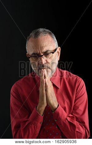 middle aged man praying man on black