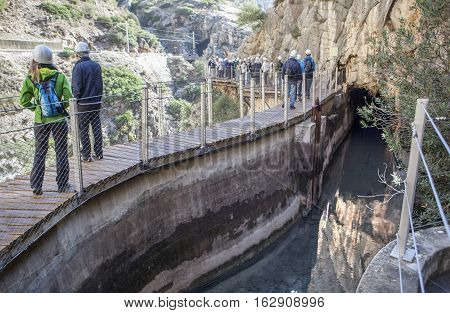 Visitors walking beside the irrigation canal along Caminito del Rey path Malaga Spain