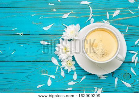 Still life with cup of coffee and flowers on light wooden table