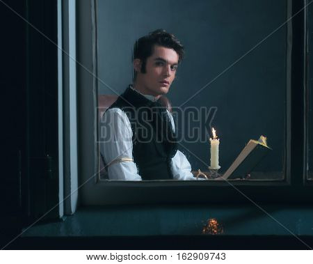 Vintage Victorian Man Sitting By Rainy Window Reading Book With Candlelight.