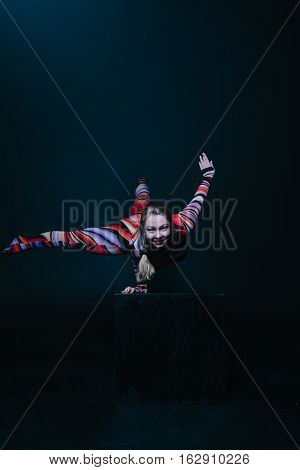 Young flexible blonde circus acrobat posing in studio in costume. Doing equilibre balance handstand on a cube. Copy space text.