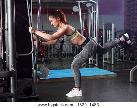 Woman Exercising With Crossover In Fitness Club Or Gym Training Legs, Buttocks.