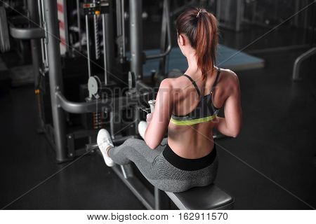 Girl Doing Exercise On The Back Muscles In A Block Simulator. Rear View Girl In The Gym.