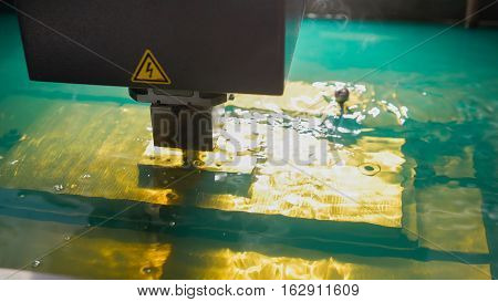 Cutting of sheet metal process in water. Sparks fly from laser by automatic factory, production, front view, close up