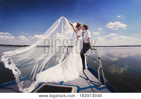 Just Married Couple On Yacht. Happy Bride And Groom On Their Wedding Day