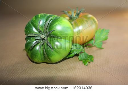 green tomatoes on a brown background unripe