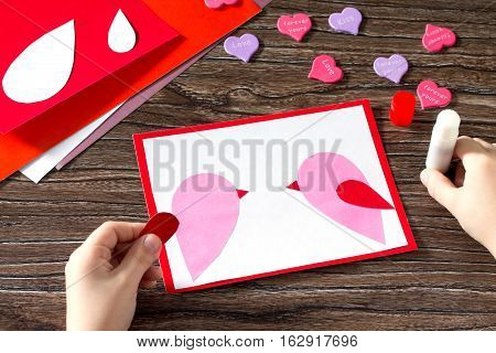 The Child Glues The Details Applique. Baby Greeting Card For Valentine's Day. Sheets Of Paper, Glue,